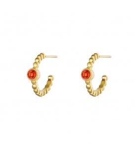 Goudkleurige ronde oorstekers met ribbels en een oranje steentje