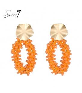 Oranje oorhangers van kralen en een goudkleurig oorstukje