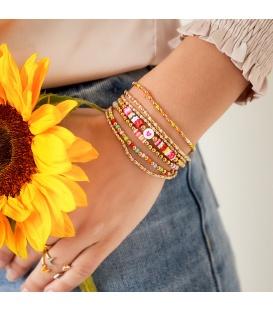 Armband met lange goudgekleurde kralen en kleine paarse kralen