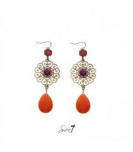Goudkleurige oorhangers met roze steentjes in bloemvorm en een oranje hanger